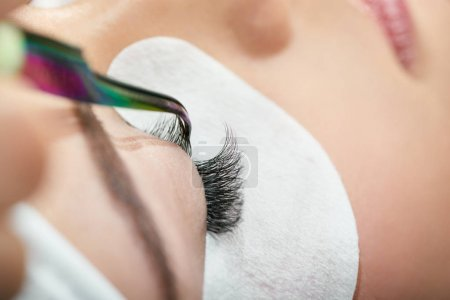 Close up of making lashes with tweezers. Womans la...