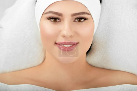Portrait of smiling woman lying on white cosmetolo...