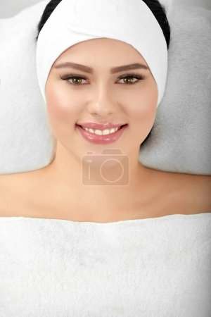 Horizontal portrait of smiling woman lying on whit...