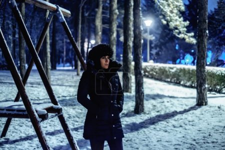 Girl standing and thinking in a park covered in snow