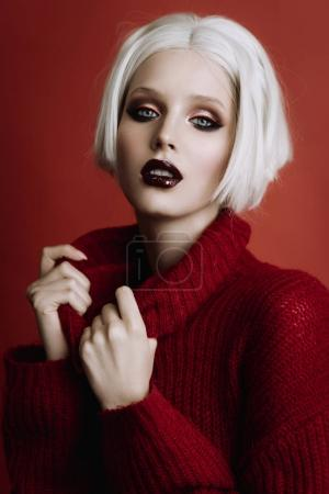 Portrait of beautiful young woman with short blond hair and fashion make-up posing