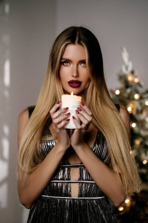 Photo for Blonde girl in a shiny evening dress with candles and gifts. The girl is dreaming. New year's night. Christmas Eve. Cozy holiday at the fur-tree with lights and gold decor - Royalty Free Image