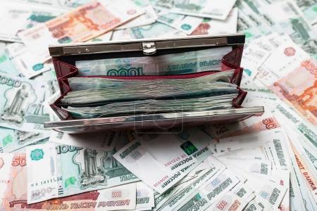 Photo pour Bourse rouge pleine d'argent sur la table beaucoup d'argent, argent russe, rouble, roubles - image libre de droit