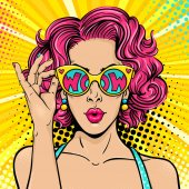 Wow pop art face Sexy surprised woman with pink curly hair and open mouth holding sunglasses in her hand with inscription wow in reflection Vector colorful background in pop art retro comic style