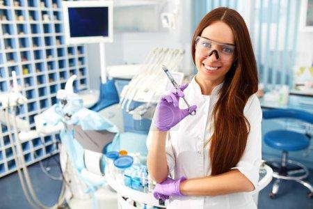 Photo pour Portrait d'une belle jeune fille sur le fond du cabinet du dentiste. Traitement orthodontique. Concept de soins dentaires. Souriez sainement. Belle sourire féminin . - image libre de droit