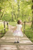 A little girl in back with a tutu dress on a wooden bridge in a forest. Wooden walkway in green forest near the Ropotamo river, Bulgaria