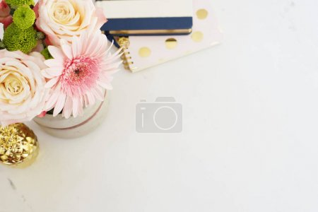 Photo for Feminine workplace concept in flat lay style with, flowers, golden pineapple, notebooks on white marble background. Top view, bright, pink and gold - Royalty Free Image