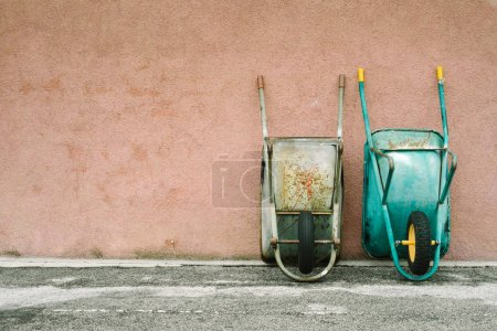 wheelbarrows leaning against wall