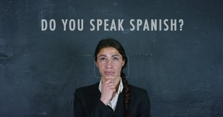 Portrait of a beautiful Spanish teacher, on a black background. Concepts: ideas, school, university, knowledge of languages, schoolchildren, teachers, memory, learn Spanish, communication and speech