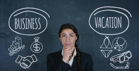 Portrait of a beautiful business girl (student) thinking of choosing a business or vacation, in the background of a black board. Concept ideas university college question choice of profession thinking