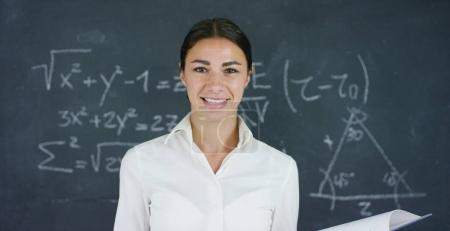 Portrait of a beautiful girl, teacher or student solves examples, formulas, triangle on a black board, on a black background. Concepts: ideas, algebra, mathematics geometry school university knowledge