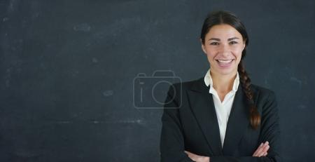 Portrait of a beautiful business girl, a marketing teacher, thinking about new ideas and strategies, on a black background. Concept: career growth, growth chart, successful girl, marketing, ideas.