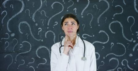 Portrait of a beautiful female doctor (student) thinking about choosing a profession, at a black board. Concept: ideas, school, university, chemistry science teachers memory biology physician question