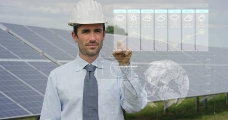 A futuristic engineer-expert in solar photovoltaic panels, uses a hologram with remote control, performs complex actions to monitor the system using clean renewable energy remote support technologies