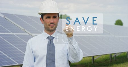 "A futuristic technical expert in solar photovoltaic panels, selects the ""Save energy"" function using pure renewable energy. The concept of remote support technology, ecology and remote control"
