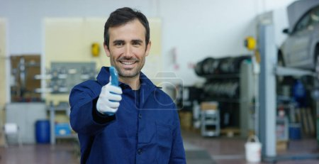 Photo for Portrait of a young beautiful car mechanic in a car workshop, in the background of service. Concept: repair of machines, fault diagnosis, repair specialist, technical maintenance and on-board computer - Royalty Free Image