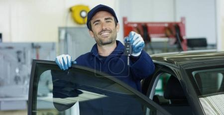 Portrait of a young beautiful car mechanic in a car-care center, with keys in his hands. Concept: repair of machines, fault diagnosis, repair specialist, technical maintenance and on-board computer.