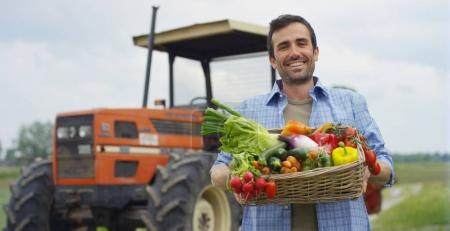 Portrait of a happy young farmer holding fresh vegetables in a basket. background of a tractor and nature Concept biological, bio products, bio ecology, grown by own hands, vegetarians, salads healthy