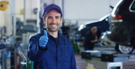 Photo pour Portrait d'un jeune beau mécanicien automobile dans un atelier automobile, en arrière-plan d'un service automobile Concept réparation de machines, diagnostic de pannes, spécialiste de la réparation, maintenance technique à bord de l'ordinateur - image libre de droit