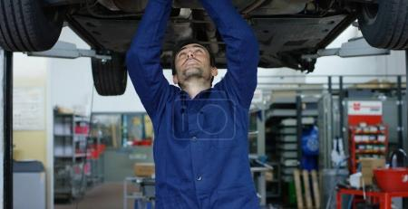 Specialist auto mechanic in the car service, repairs the car, makes transmission and wheels. Concept: repair of machines, fault diagnosis, repair specialist, technical maintenance, on-board computer.
