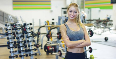 Young beautiful girl in the gym, stands smiling after coaching, satisfied and relaxed, proud of her achievements. Concept: love sports, to attend a gym, proper nutrition, a slender body, to be healthy