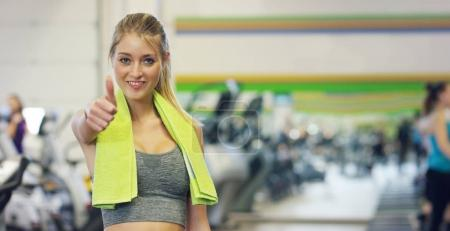 Young beautiful girl in the gym, stands smiling with a towel on her shoulder after the coaching and relaxed. Concept: to love sports, to attend a gym, proper nutrition, a slender body, to be healthy.
