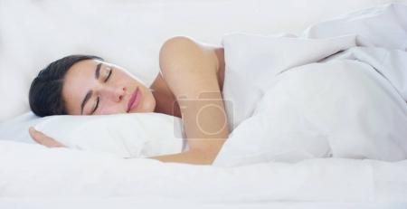 A simple day off for a beautiful young girl sleeping in a warm bed, covered with a soft warm white blanket, on a white background.