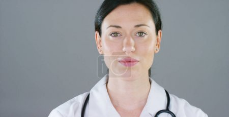 Portrait of a female doctor with white coat and stethoscope smiling looking into camera on white background. Concept: doctor, health care, love of medicine.