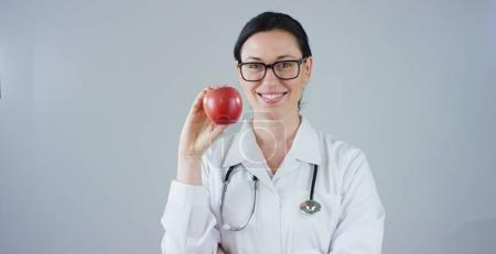 portrait of a nutritionist, an expert on food and health welfare, smiles looking into camera and holding an apple on a white background. Concept: diet, healthy, health food, healthy weight