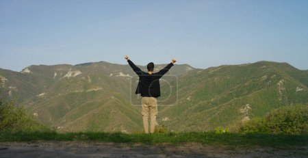 Happy young man, cry from the heart, feels free and independent , on the background of beautiful high mountains and sky, the concept: nature, traditional, bio, ecology.