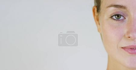 Foto de Retrato de una hermosa joven sonriendo y mirando a la cámara, sin maquillaje, después crema, sobre fondo blanco. Concepto: belleza, juventud, cuidado de la piel, siempre jóvenes, amarse a uno mismo. - Imagen libre de derechos