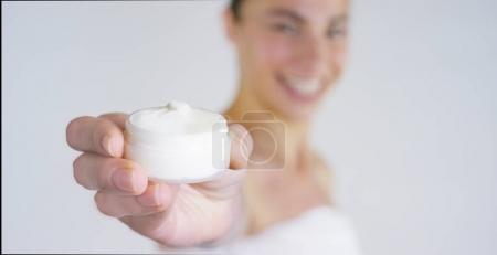 Portrait of a beautiful young girl, in close-up shows cream and smiling, on white background. Concept: vitamins, fresh, fitness, bio products, spa procedures, skin care, love yourself, cramping cream.