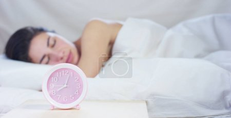A simple working day for a beautiful young girl sleeping in a warm bed, covered with a soft warm white blanket, on a white background.