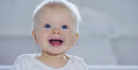 A baby, a boy with large blue eyes and light-colored hair, sits and smiles on a snow-white blanket, looks at her mother, on a white background.
