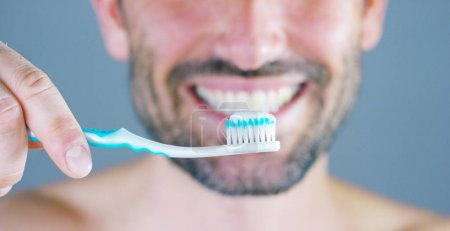 A beautiful portrait of man smiles and shines his white teeth showing his toothbrush and dentrifricio for I lost teeth advised by his dentist. Concept: beauty, dentist, oral hygiene