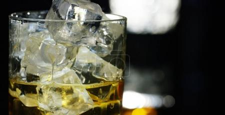 Photo pour Whisky versé dans un verre avec de la glace, au ralenti, prise de vue macro, sur une table en bois et fond sombre. Concept : alcool, spiritueux, pour une bonne soirée, l'alcool nuit à la santé. - image libre de droit