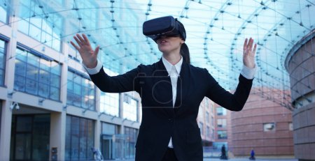 Photo for A beautiful career woman uses virtual reality, in the background the business centre. The business woman playing and having fun with augmented reality. Concept: insurance, business,immersive technolog - Royalty Free Image