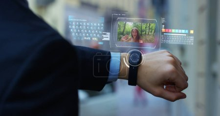 A man answers the wife who smiles and waves from the phone that appears in hologram clock futuristic and technological. Concept: holiday, communication,family, technology, augmented reality and future