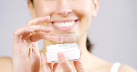 Photo pour Le portrait d'une jeune femme à la peau parfaite appliquant une crème jour / nuit sur son visage préalablement nettoyé. Concept de soins de la peau, cosmétiques, beauté, centre de bien-être, soins du visage, massage facial - image libre de droit