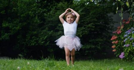 Photo pour Petite fille essaie de faire les premiers pas danseur dans un jardin habillé comme un petit danseur danseur heureux drôle. concept premiers pas et bonne enfance nature. petits enfants drôles. caméra cinéma - image libre de droit
