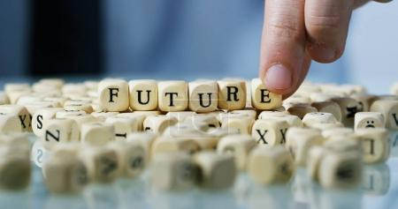 """Slow motion macro of the word """"Future"""" made of the wooden letter blocks . Concept of financial market and future of stock market business."""