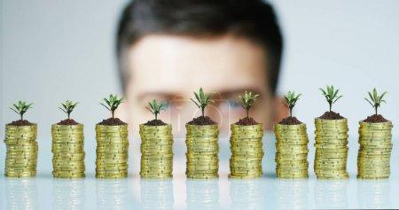 Photo pour Homme d'affaires dans une macro shoot ci-dessus pour cacher la pile de pièces dans les semis. Concept : gains ou revenus, banque d'investissement, financement et prêts sans intérêt . - image libre de droit