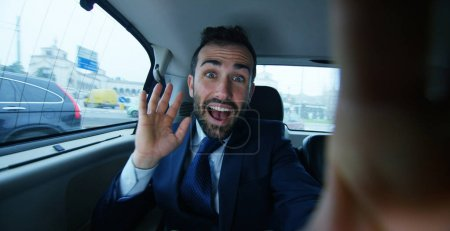 A businessman while traveling by car in the back seat, family video calls with your mobile phone. The man in the driver career for his business trips.Concept of transport, business, wealth, technology