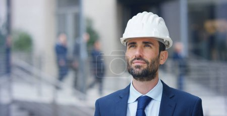 Engineer with the construction helmet, smiling proudly of its construction recently concluded, in the background is the built skyscraper. Concept:construction,business, future,passion and engineering.