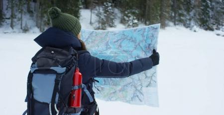 le mouvement lent d'une jeune fille se promène à travers les bois et dans la neige, respirer l'air pur, sourires de la nature de la montagne, est à pied avec sac à dos de randonnée. Concept: détente, randonnée, amour, pureté, liberté
