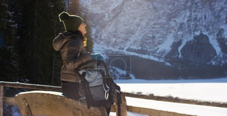 slow motion of A girl walks through the woods and in the snow, breathe pure air, smiles in the nature of the mountain, is walking with hiking backpack.Concept:relaxation, hiking, love, purity, freedom