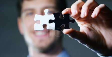 A businessman in a suit holding a white puzzle piece and a black unites them. Concept: diversity, team work, racism, and access solution.