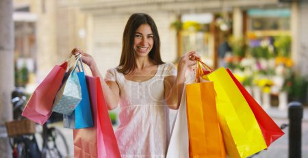 A beautiful woman walks through the city on shopping, she is very happy of purchases in the period sales. Concept: fashion, shopping, happiness and fashion bloggers
