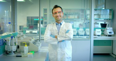 nice young scientist male doctor analyzing liquids virus cells in professional laboratory using qualified equipment and wearing glasses to protect eyes and taking care of the lab glasses