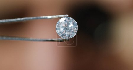 A goldsmith in jewelry checks the quality of luxury brilliant diamonds. The diamonds of high caliber shine the light and pure. Concept: Jewelry, luxury, glitz, gloss and goldsmith.